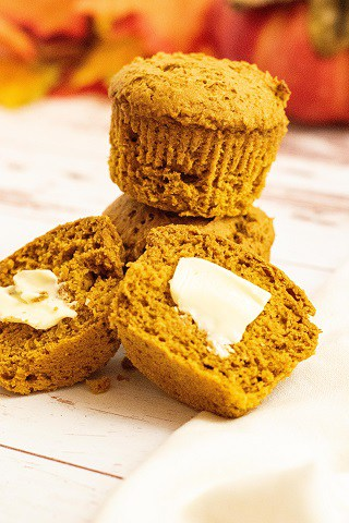 A stack of pumpkin muffins one is cut in half and buttered