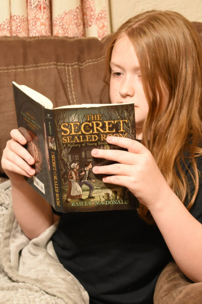 """A young boy sitting on a couch reading the book """"The Secret of the Sealed Room"""""""