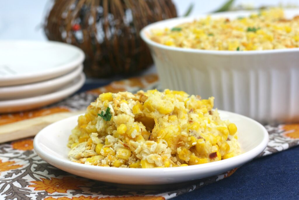 a white plate with corn casserole on top.