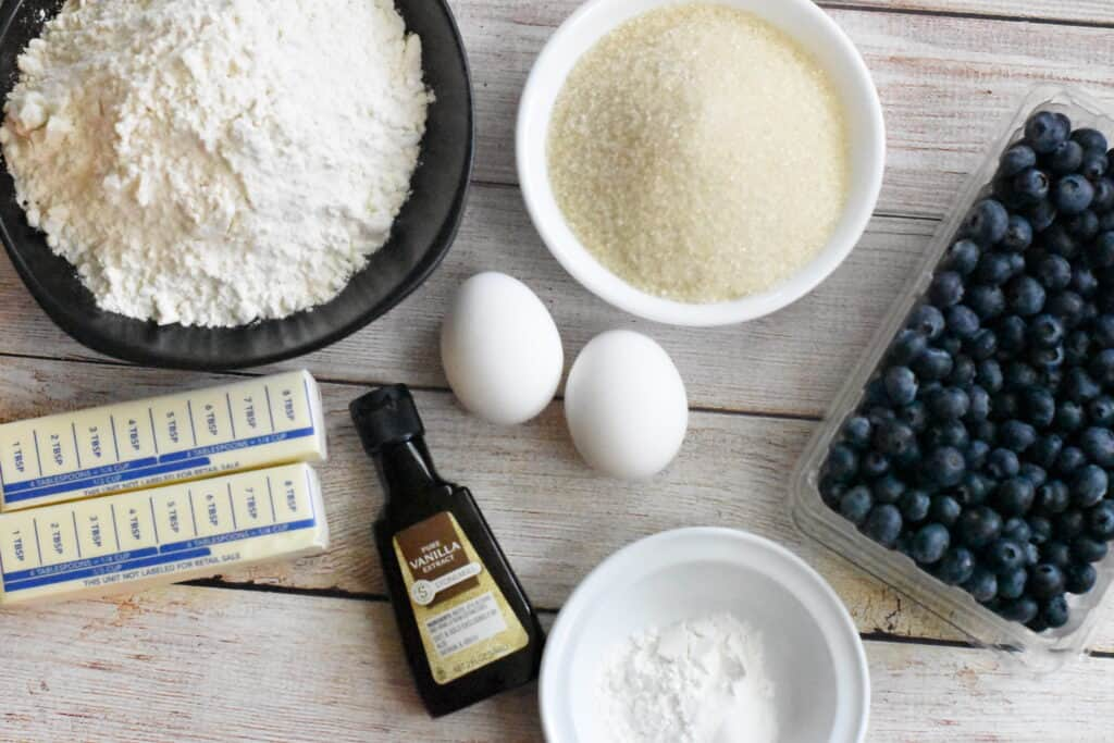 Ingredients for blueberry bread, butter, eggs, vanilla, sugar, blueberries on a wooden background