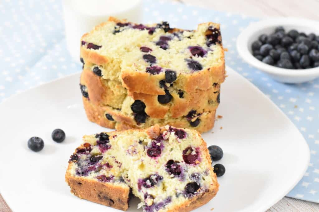 Blueberry bread on a white plate with a bowl of blueberries in the background