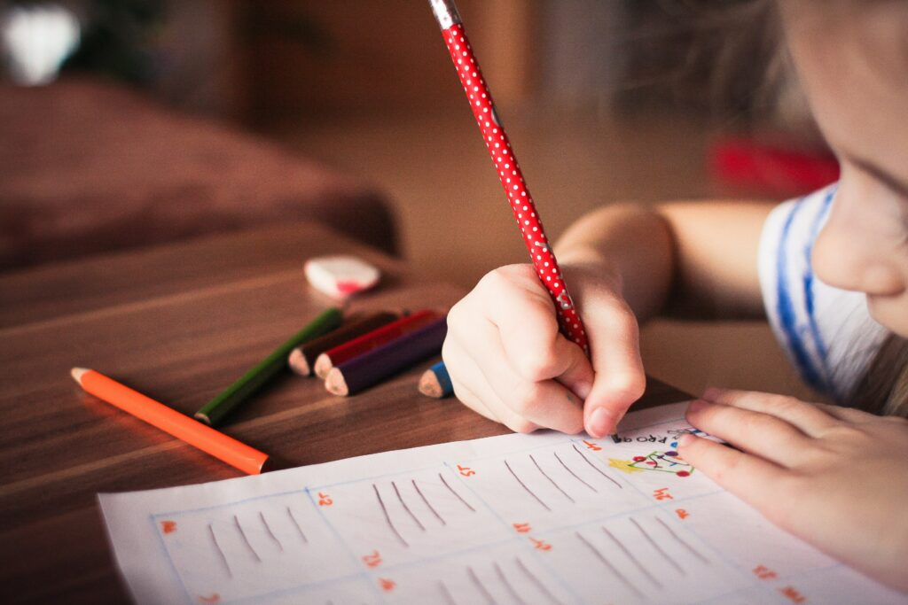 A young girl working on a worksheet with a red pencil at a table.