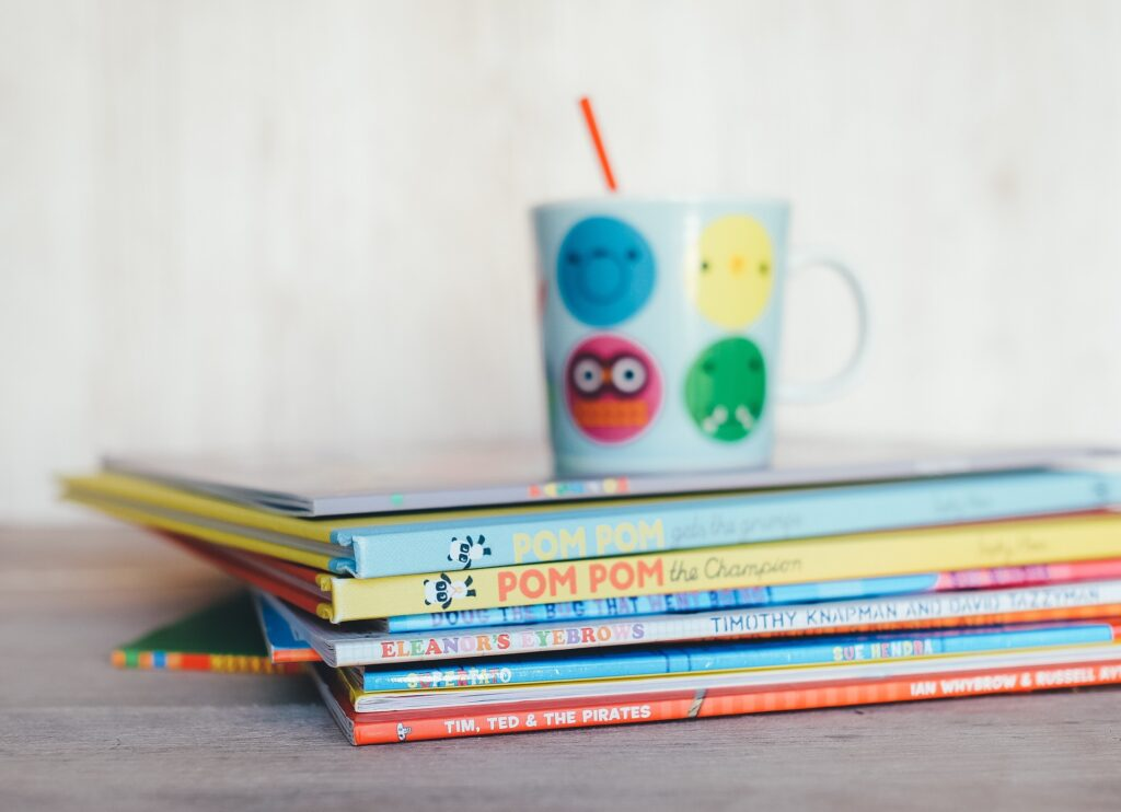 A pile of colorful kid's books with a colorful mug on top