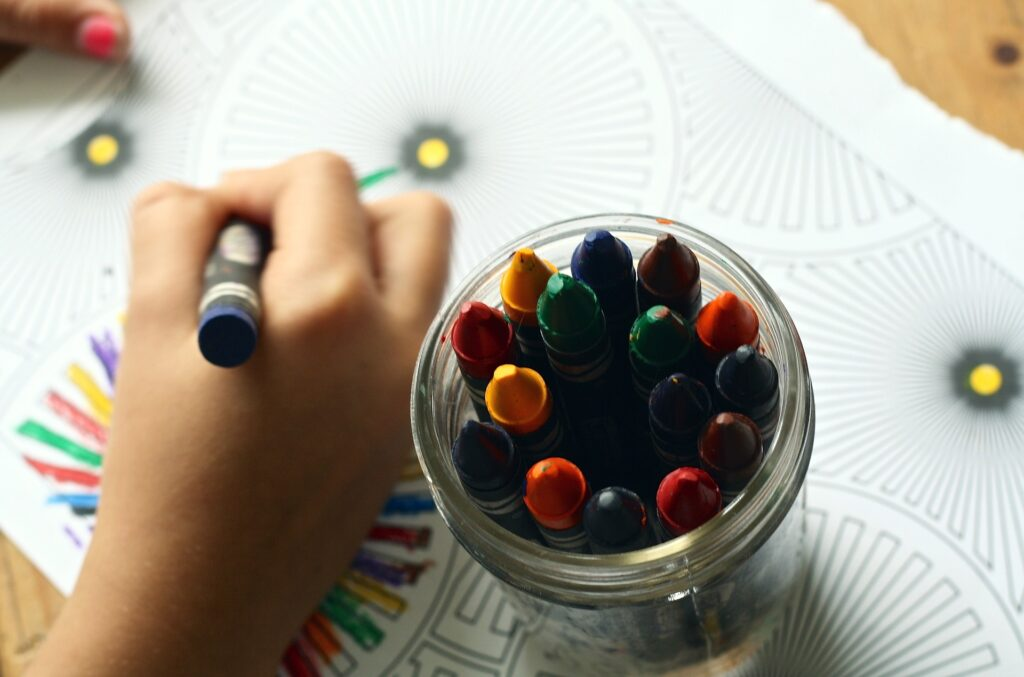 A jar full of crayons with a hand coloring a coloring page