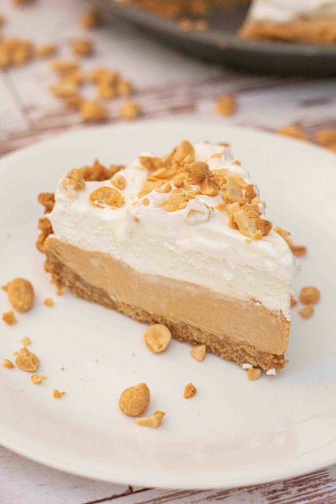 Piece of peanut butter pie topped with cool whip and chopped peanuts on a white plate.