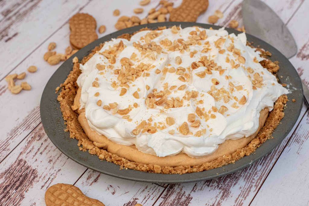 Whole peanut butter pie topped with cool whip and chopped peanuts surrounded by peanuts and nutter butter cookies