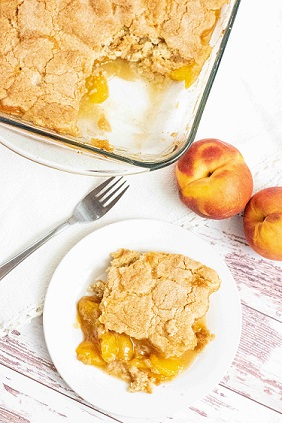 A white plate with a piece of peach cobbler sitting next to a pan of peach cobbler with a portion removed