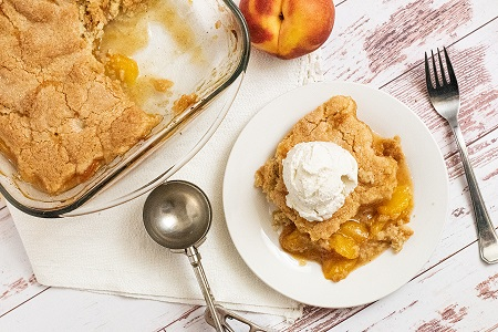 A white plate with a piece of peach cobbler with a scoop of ice cream on top.