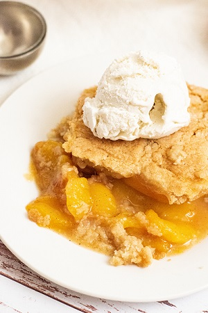 A piece of peach cobbler with a scoop of vanilla ice cream on the top