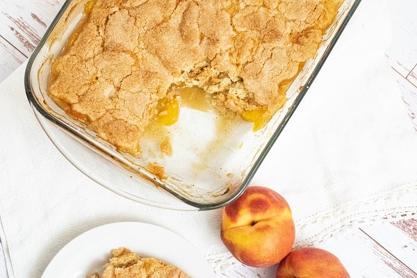 A pan of peach cobbler with a serving removed
