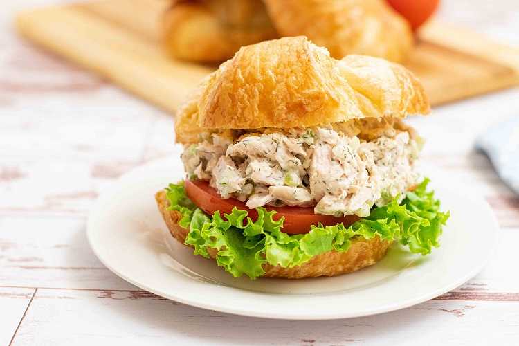 a tuna salad sandwich with tomato and lettuce on a crossiant on a white plate
