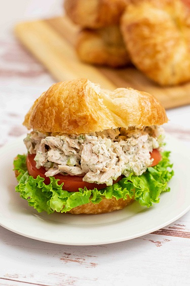 tuna salad with tomato and lettuce on a crossiant on a white plate