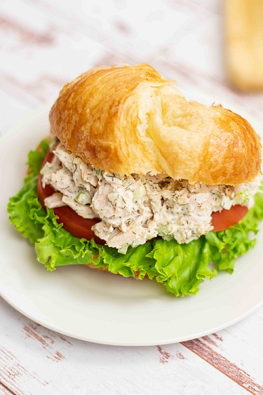 a crossiant with tuna salad lettuce and tomato on a white plate