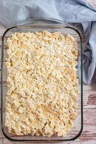 A glass baking dish full of creamy, cheesy, potato mixture