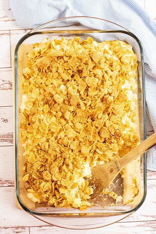 A glass casserole dish full of funeral potato casserole with a wooden spoon