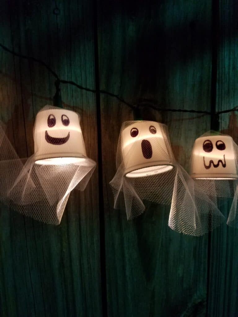 Ghost party lights hanging on a fence