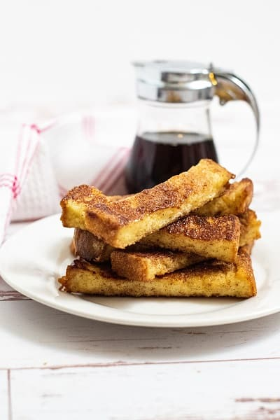 A pile of french toast sticks on a white plate with maple syrup in the background