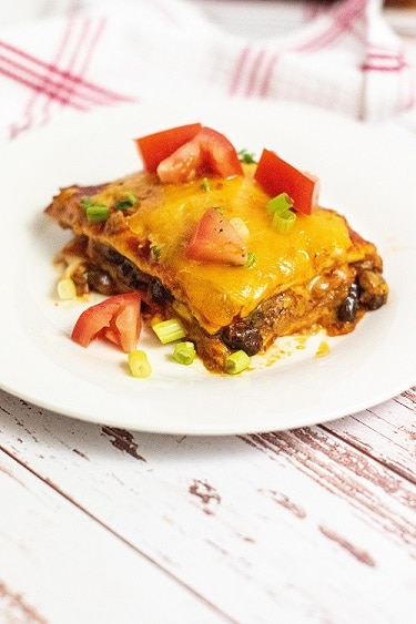 A piece of enchilada casserole on a white plate