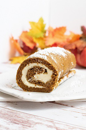 a pumpkin roll with pumpkins in the back ground.