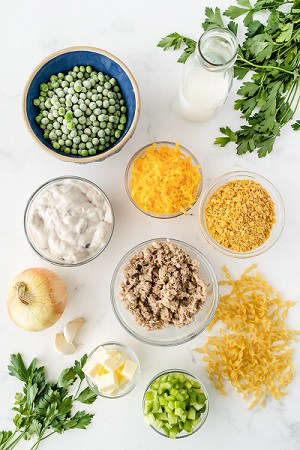 The ingredients for tuna casserole in seperate bowls, peas, shredded cheese, cream of mushroom soup, crushed cornflakes, tuna, noodles, onion, garlic, butter, celery and parsley