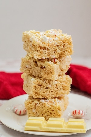 A white plate with rice krispie treats stacke on it with a chunk of white chocolate beside them