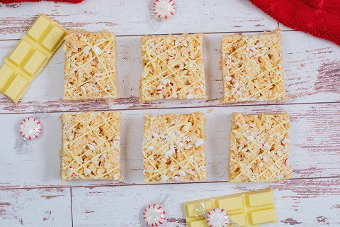 6 rice krispie treats lined up on a wooden background
