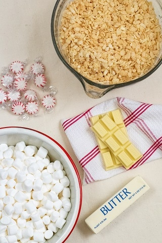 The ingredients for white chocolate peppermint rice krispie treats. Rice krispies, peppermints, white chocolate chunks, marshmallows and a stick of butter