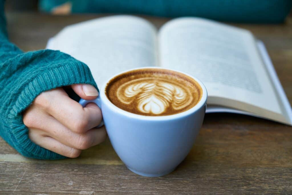 A hand holding a mug of coffee with a book in the background
