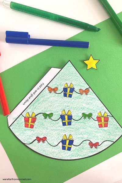 A cone christmas tree laying flat on a green background with crayons and markers around it