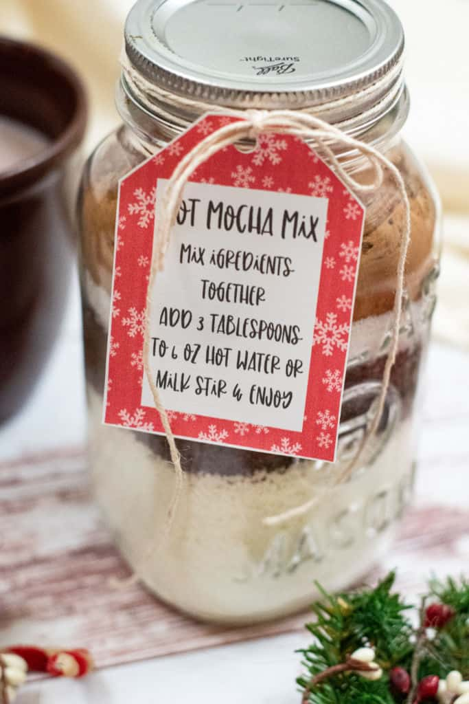 A mason jar full of layered ingredients. There is a gift tag with instructions tied to the top with a piece of twine