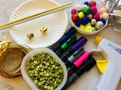 Supplies for diy noisemakers, paper plates, paper straws, pom poms, paint pins, glue gun, dried beans, ribbon