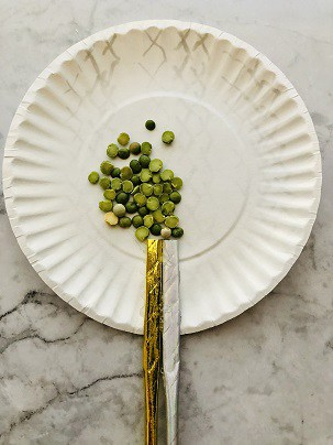 Paper plate with dried peas and paper straw