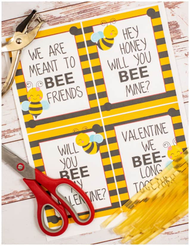 Printed bee valentines with a hole punch, scissors and honey straws.