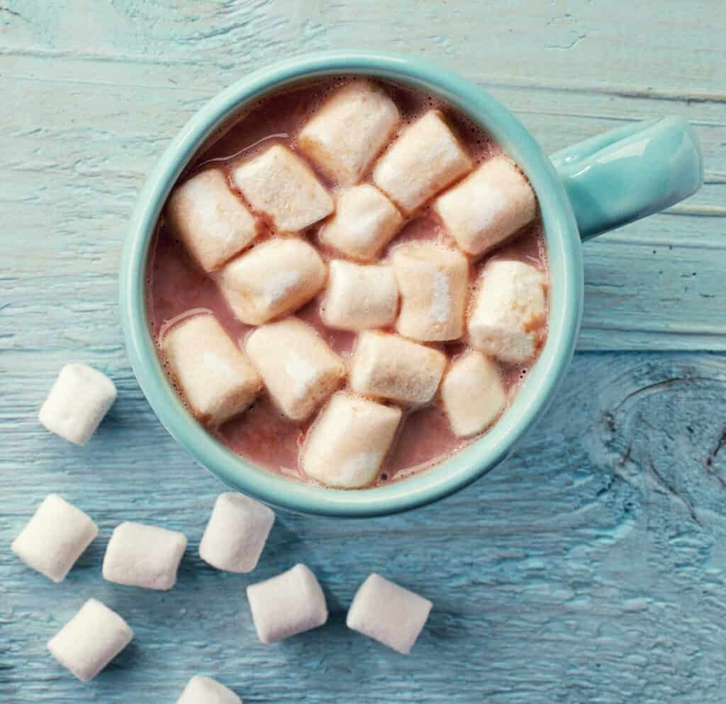 A blue mug full of hot cocoa and marshmallows.