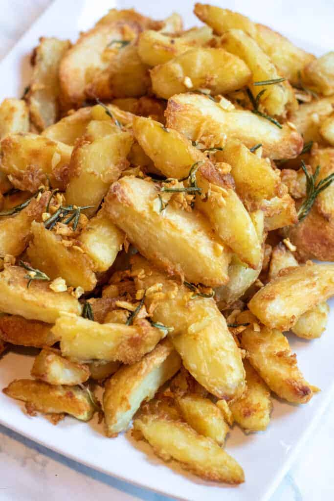 a plate full of crispy potato wedges garnished with rosemary