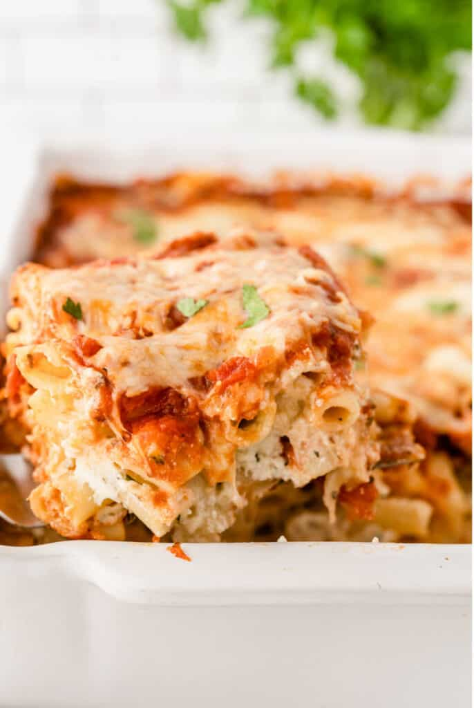 a piece of baked ziti being dished out of a pan