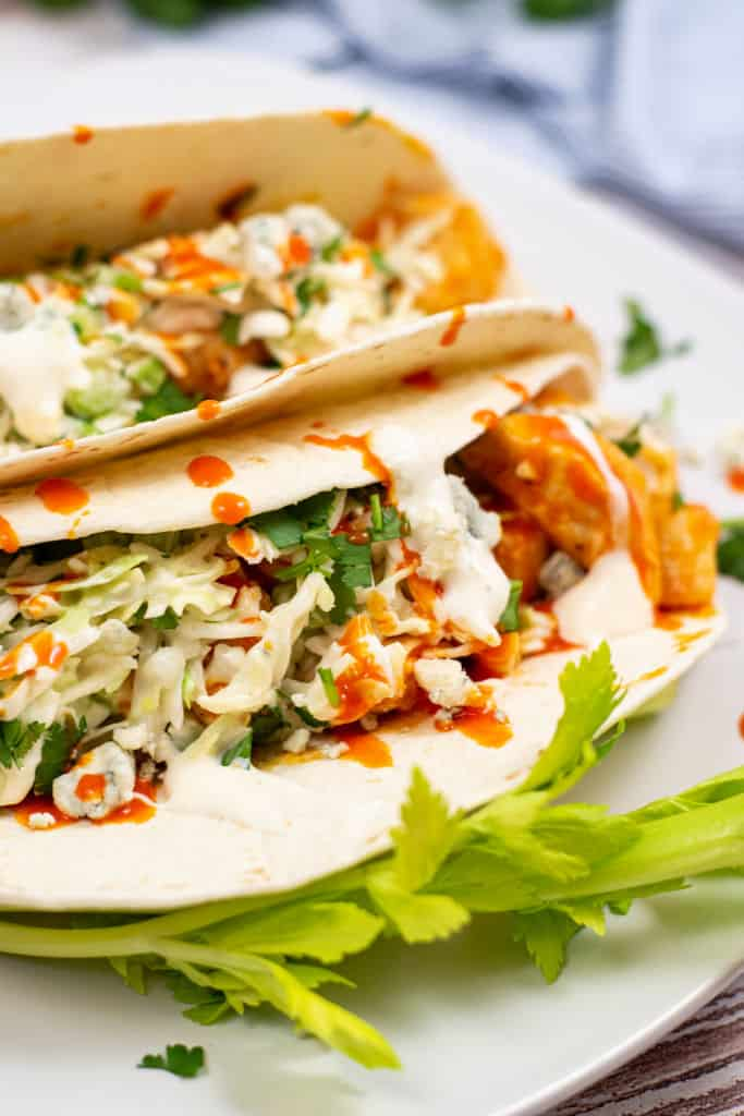 Two tacos on a white plate filled with buffalo chicken, coleslaw, blue cheese and buffalo sauce garniches with celery