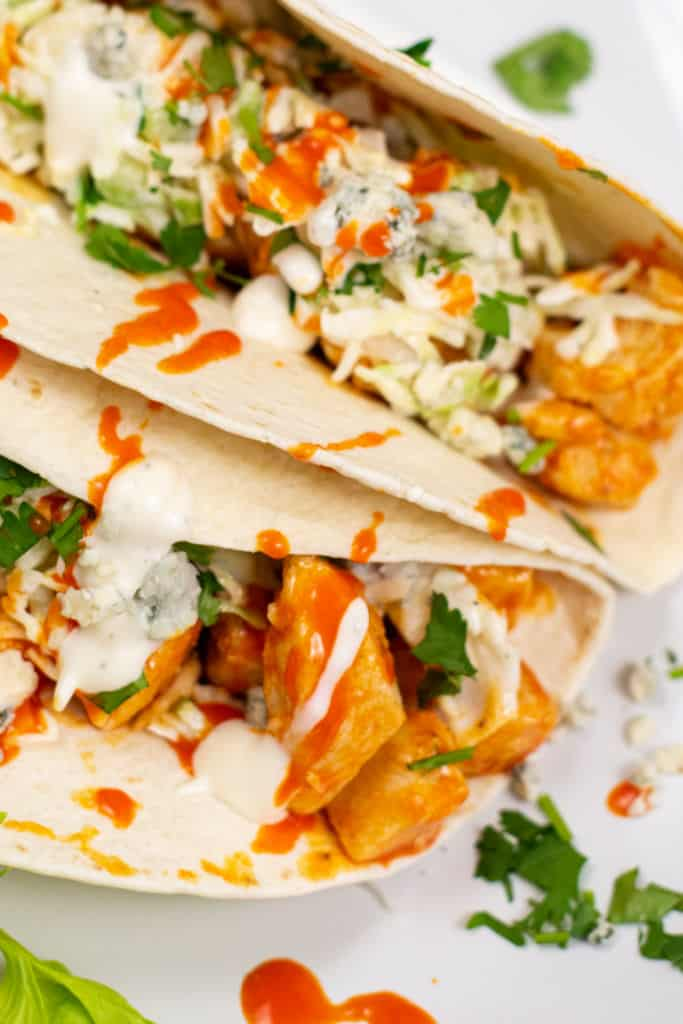 Two soft tacos filled with buffalo chicken and coleslaw on a white plate.