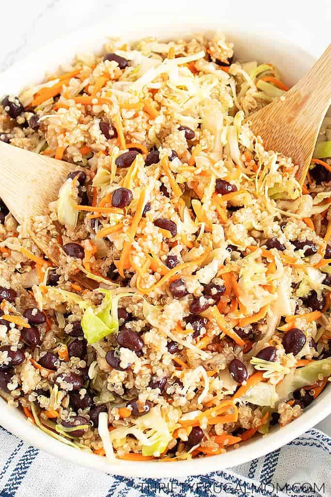 A white bowl full of salad with quinoa, cabbage, carrots and beans, there are 2 wooden spoons in the bowl