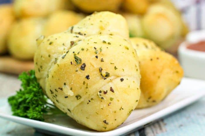 a white plate with garlic knots on it, garnished with parsley