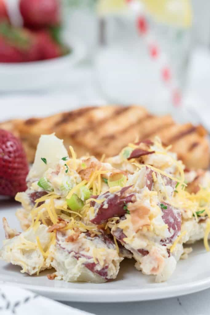 A white plate with potato salad grilled chicken, and strawberries.