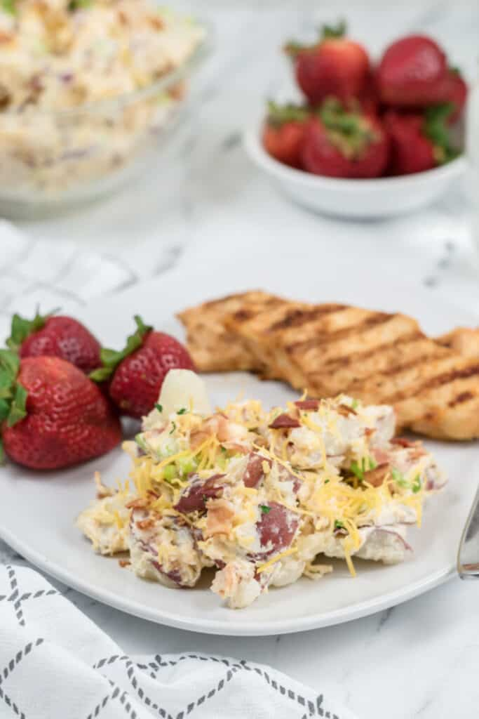 A white plate with potato salad, grilled chicken and strawberries