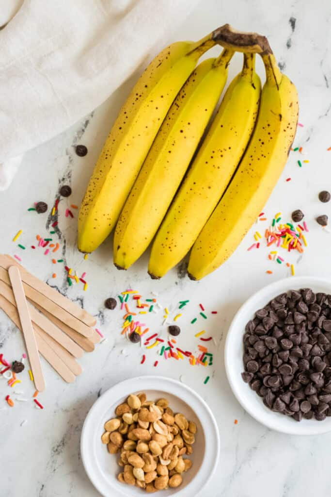 The ingredients for making chocolate covered banana pops. Ripe bananas chocolate chips sprinkles, chopped peanuts and popsicle sticks arranged on a marble countertop
