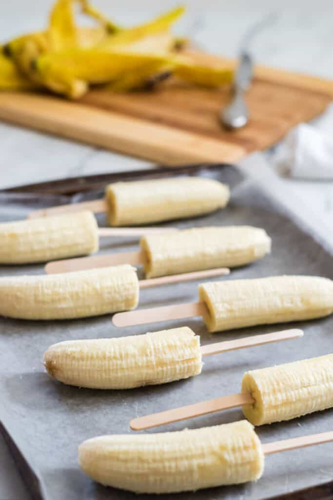 A tray full of peeled halved bananas on popsicle sticks