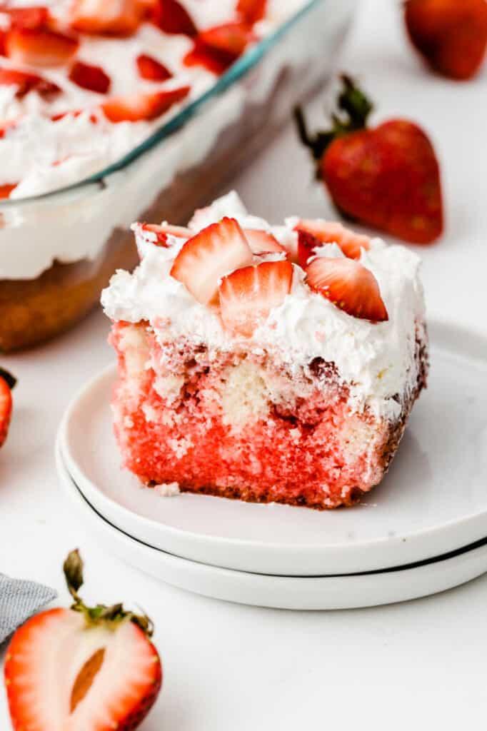 A piece of strawberry shortcake poke cake sitting on a white plate