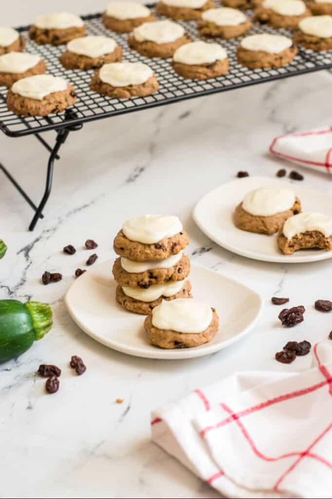 A white plate with a stack of frosted zucchini cookies. In the background is a cooling rack covered with zucchini cookies