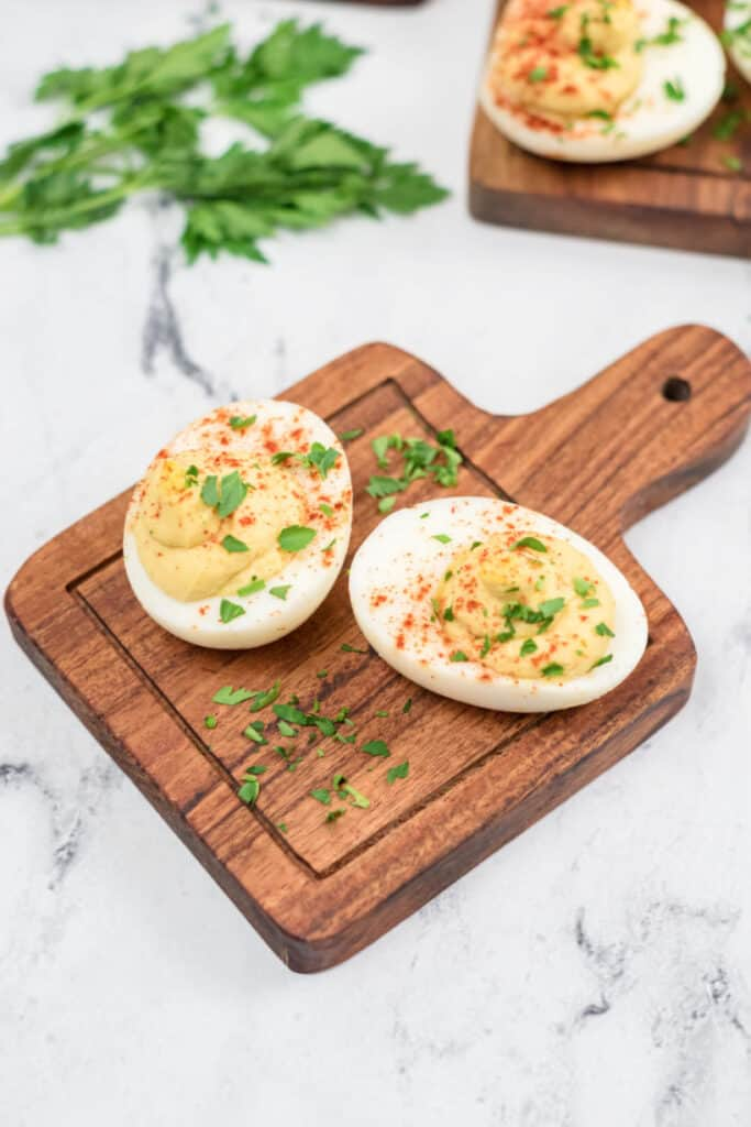 2 deviled eggs on a small wooden board