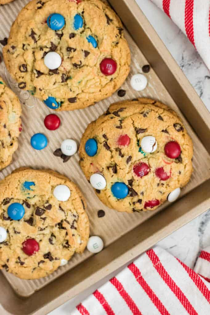 Red white & blue M&M cookies on a cookie sheet