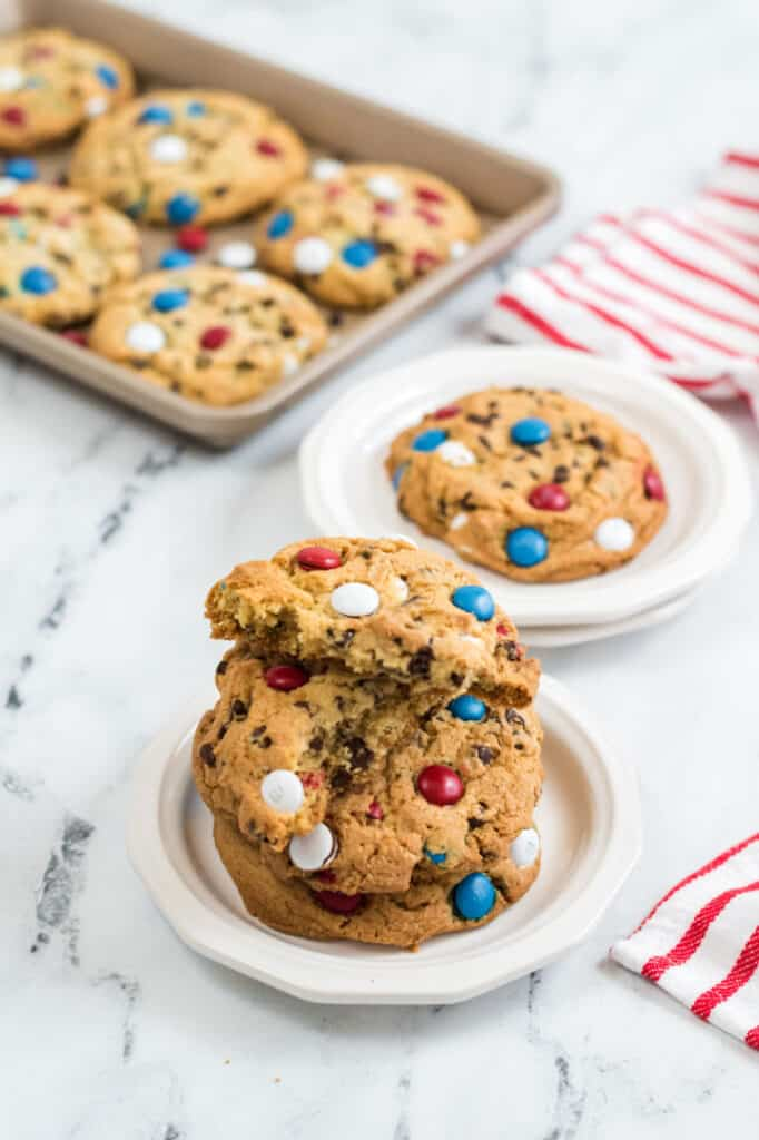 Giant M&M Cookies on white plates with a red and white linen next to them