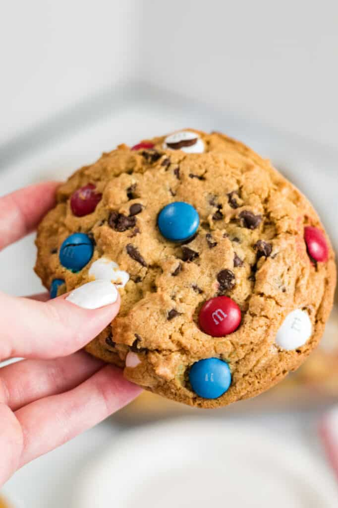 A hand holding a giant M&M cookie
